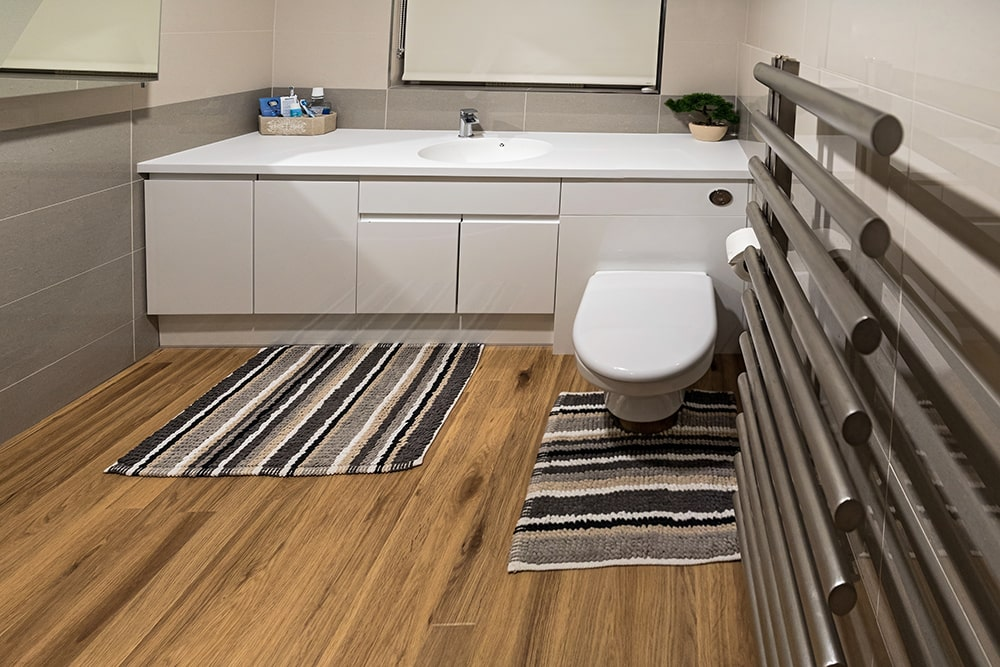 Image of a toilet, sink and bath mats
